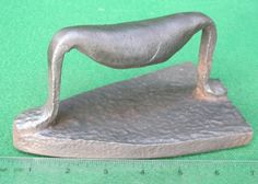 This primitive, blacksmith forged sadiron is also called a 'slave iron' or  'tattle-tale bell' iron due to the small metal pea or ball that rattles inside the hammered and rolled hollow handle when the iron moves.  The story goes that as long as the mistress of the house could hear the rattle on ironing day, she knew the servants were working.