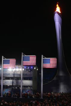 Three American flags are raised for the silver medalist Gus Kenworthy of the United States, gold medalist Joss Christensen of the United States and bronze medalist Nicholas Goepper of the United States infront of the Olympic flame during the medal ceremony for the Freestyle Skiing Men's Ski Slopestyle (c) Getty Images