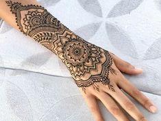 Henna Tattoo in schwarzer Farbe, Arm- und Handgelenktattoo mit floralen Motiven, tätowierte Frau