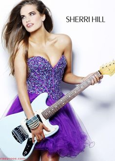 Interesting pose with prop with mini dress. Note the lighting on the collar bones with slight shrug. Hard light on camera left is filled with light from camera right (see under chin and jaw). A more traditional studio fashion look. The line made by the guitar neck aligns with the line made by the jaw.