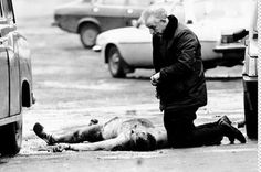 A Catholic priest alongside the body of Corporal David Howes—after his execution by the Provisional IRA.