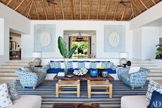 At a Punta Mita, Mexico, retreat decorated by Martyn Lawrence Bullard, the living room sofa, with seat and back cushions of Chameleon fabric by Perennials, is flanked by custom-made chairs upholstered in Kaba Kaba linen by Bullard. The striped rug brings the room's color palette together.