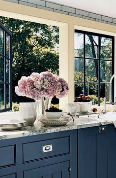 Marble counters paired with cobalt blue cabinets complement the captivating views of this country kitchen. The lack of a good view (or one at all for that matter) doesn& mean a compromise on the deco Decor, House Design, House, Kitchen Window, Kitchen Window Treatments, Pretty Kitchen, Country Kitchen, Sweet Home, Home Kitchens