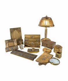"""An American Art Nouveau gilt bronze """"Abalone"""" pattern desk set by, Tiffany Studios decorated with inlaid abalone with in each piece. The set comprises of a letter rack, picture frame, calendar frame, pen tray, letter opener, blotter ends, rocker blotter, inkwell, pen wipe, postage scale, stamp box, utility box with key, memo pad, magnify glass, and a linenfold desk lamp. Each piece is signed, Tiffany Studios New York"""" and all are numbered.   circa 1900"""