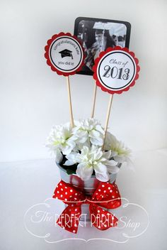 Graduation Centerpiece Stick. Decorate your graduation party with these centerpiece sticks to carry out your party theme. Use a galvanized bucket, Styrofoam, silk flowers as well as a pretty ribbon to finish off your pretty party table decor.