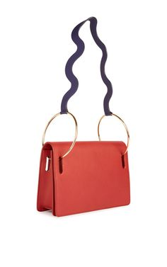 This **Roksanda** bag is rendered in leather and features a shoulder strap attached to prominent gold hoops.