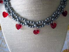 4mm gray glass pearls are woven to 6mm gray glass pearls. It's accented with gray glass seed beads and ruby red glass crystal hearts that will sparkle in any light. Each heart is hand wrapped with special care. $30.00 #weddings #jewelry #necklace #bridesmaid-gifts #gray-woven-necklace #woven-necklace #bridal-accessories #ruby-red-hearts #hoilday #prom #accessories #valentines-day #crystals #genuine-crystals #hand-wrapped #goth #fantasy #women #handmade