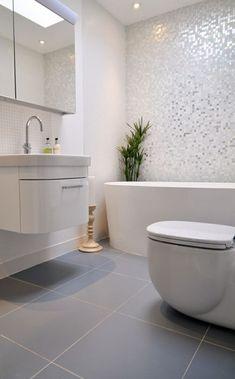 Salle de bain blanche avec mosaïque murale blanc nacré et WC suspendus