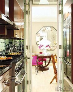 The cherry-veneered cabinetry in the kitchen was designed by Caravelli, and the refrigerator is by Sub-Zero; the living room's octagonal mirror is by Gerald Bland.   - ELLEDecor.com