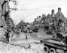 Convoi du 300th Combat Engineers dans les ruines de Isigny-sur-Mer, Place Gambetta, aujourd'hui Place de Gaulle, 19 june 1944.