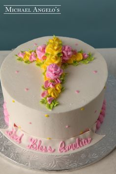 Yellow & Pink Cross #51Religious This cake is a more traditional design and is perfect for a small get together. The top of the cake features a beautiful cluster of buttercream flowers in the shape of a cross.