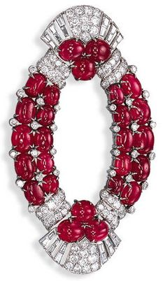 AN ART DECO RUBY AND DIAMOND BROOCH  Designed as a cabochon ruby open oval panel, enhanced by collet diamonds, to the circular and baguette-cut diamond flared terminals, circa 1925, with French assay marks