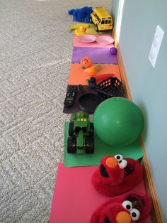 Toddler color scavenger hunt with construction paper on the floor and their toys.