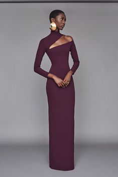 Solace London Ares Dress Aubergine from Fall Winter Sleek long-sleeve column dress with graphic shoulder cut-out and a high-neck, designed with a signature high kick split for ease of movement.