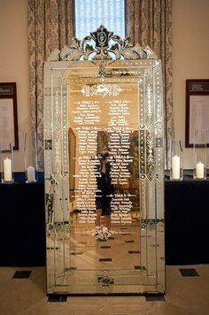Guests' table assignments are calligraphed on a beautiful ornate mirror and framed by an intricate custom design.