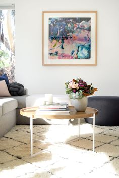 Contemporary Australian living room with large abstract wall art, minimalist coffee table with white frame and timber top. Get our top coffee table styling tips now!