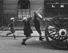 Young boys hitch a ride, London, 1941.   vintage everyday: Children Playing – Vintage Photos of Children's Fun That Could Have Lost Today