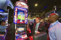 """People look over a """"Ferris Bueller's Day Off """" video slot machines by WMS Gaming during the G2E convention at the Sands Expo Center Tuesday,..."""
