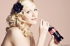 pinup hair style, drinking coca cola.