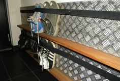 Shoe organization idea for a narrow closet:  aluminum stair tread, narrow ledge, and a wide elastic band.