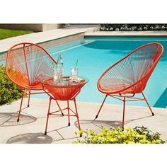 Evoking a seashell, this 3-piece orange metal outdoor table and chair set is a bold, postmodern look for the patio.