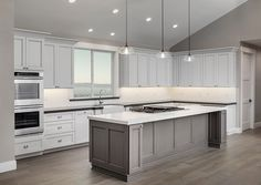 L shaped kitchen layout with island and white cabinets and two types of countertops