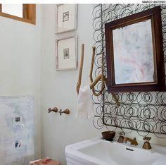A estrutura de molas de colchão – encontrada em uma caçamba na rua – foi limpa, envernizada e virou um painel no lavabo. No lugar do porta-toalha convencional, um galho torto. Na parede, fotos de família. Projeto da arquiteta Kita Flórido.