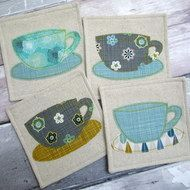 Retro inspired coasters with grey, mustard and blue printed cotton fabric.  These 4 coasters would make the perfect gift for someone special and are an ideal present at any time of the year. The coasters each have a tea cup & saucer appliquéd in 10...