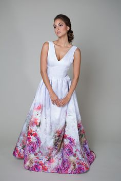 This a-line wedding gown features a v-neck bodice and an open v-back, a natural waist, full gathered skirt, pockets, and features a beautiful floral print that is hand screened in Italy. * Photographed In: Purple * Color Options: Purple * Fabric: Silkscreen * Silhouette: A-