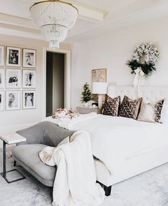 Beautiful master bedroom with white bedding and gallery wall