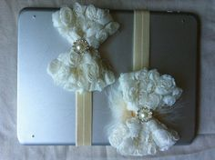 Ivory shabby flower bow with embellishment attached to ivory fold over elastic. Can be made with or without feather
