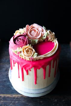 Tall pink ombre drip cake with swiss meringue buttercream flowers and hot pink chocolate ganache