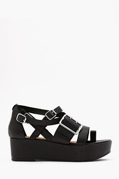 "Leonola Platform Sandal: Super chic black leather platform sandal featuring strapped and silver buckled detailing. Strap at toe, genuine leather insole. Looks rad paired with a chiffon dress and moto jacket! By Jeffrey Campbell.         *Genuine leather   *Shoe Height: 5.65""  *Platform Height: 2""  *Runs true to size  *Imported"