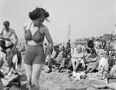 A young woman in a knitted bathing costume stands on the beach in the midst of the crowds of holidaymakers, Blackpool