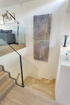 Verschieben die natürlichen Holz Treppe hinunter vom Wohnzimmer, sehen wir, wie der rahmenlosen Glas-Brüstung visuelle Linien offen im ganzen Haus hält. Die offene, luftige Natur dieser Elemente hilft den abgeschotteter Raum mehr expansive fühlen.