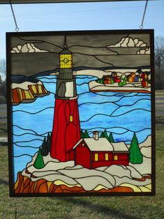 """Winter Lighthouse - Copper foil stained glass panel (24"""" wide X 28"""" high) in oak frame based on a pattern from Paned Expressions Studio """"Our Favorite Patterns"""" CD."""