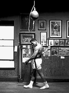 Cassius Marcellus Clay, Jr. Camino como campeón, frente en alto, hombros bajos y manos en los bolsillos.