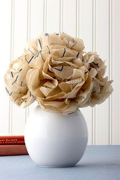 An elementary school craft takes on a sophisticated edge when fashioned from the tissue-thin paper of old sewing patterns.  Step 1: For each flower, cut six 7-inch squares from the pattern. Stack and fold them accordion-style six times, forming a one-by seven-inch rectangle. Snip off the corners of the rectangle with scissors.   Step 2: Tightly twist a wire floral stem around the center of the rectangle.   Step 3: Fan out the paper, then pull apart each layer, creating the blossom.