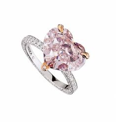 Messika Heart pink diamond engagement ring with rose gold prongs and a diamond pavé band.