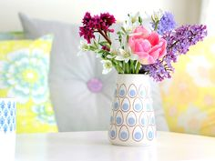 fresh flowers in sweet vase & colorful throw pillows.