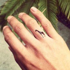 Pequeño Tatuaje en el dedo de una pequeña jirafa.