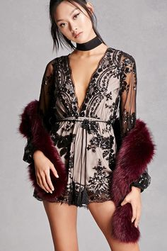 A knit romper featuring a mesh overlay with sequins, a plunging neckline, scalloped trim, an elasticized waist, a removable tasseled belt, and long mesh sleeves with cuffs. This is an independent brand and not a Forever 21 branded item.