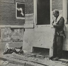 A grief-stricken father sees the body of his daughter after the Nazi bombing of Rotterdam, The Netherlands.