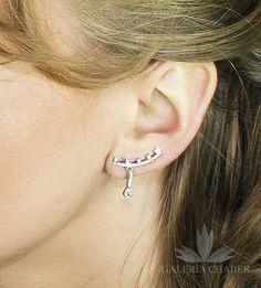 Kolczyki wiszące wykonane ze srebra próby 925, rodowane, wysadzane cyrkoniami o szlifie brylantowym. Długość całkowita elementu stałego to około 2,0 cm, długość sopla wiszącego to około 1,2 cm. Kolczyki można nosić na dwa sposoby, wzdłuż ucha oraz w formie wiszącej swobodnie.