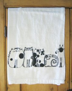 Five cat friends in a row printed on nice quality 100% Cotton, white Kitchen Towel. Towel is appx 30X30, design is center bottom edge, appx 11 across.  Please note, the design on the towel is like a picture and is not an overall design covering the entire towel. The towel is large because it is meant to be used, the design is meant to be shown when towel is folded over an oven handle or towel rack. Five Cats are about 11 long and about 6 high, center, bottom.