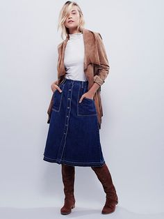 Making Me Crazy Denim Midi | Button-down denim midi skirt with a flattering A-line silhouette and four-pocket design. Deep apron-style front pockets and a raw hem complete the look.
