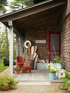 a Cozy and Rustic Cabin in Massachusetts Simple enamel buckets make for cachepots with laid-back charm on this porch.Simple enamel buckets make for cachepots with laid-back charm on this porch. Lake Cabins, Cabins And Cottages, Ideas De Cabina, Patio Wedding, Haus Am See, Lake Cottage, Cottage Porch, Lakeside Cottage, House With Porch
