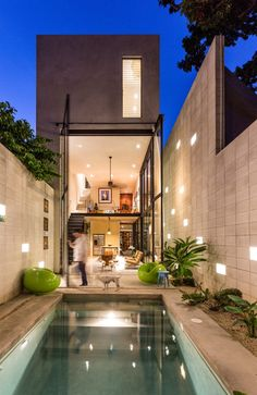 """The back of the home glows at night as the giant, two-story glass doors swing open to remove the barrier between inside and out. A polished concrete patio deck and pool, along with a simple block perimeter wall, make smart use of available materials. The pool acts as a passive conditioning tool, cooling air before it enters the house. The block wall is positioned 31 inches from the house, creating a gap or """"air chimney"""" that allows air to circulate up and away from the home, while…"""
