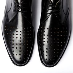 """Left shoe!!! Right shoe!!!,"" by artist Liam Gillick consists of a pair of sleek black leather brogues with perforated holes in the toe-box...."