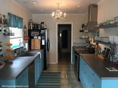 Beautiful industrial chic kitchen remodel. Concrete countertops, concrete floating shelves, IKEA Rail system, ocean blue custom painted cabinets. Gorgeous.